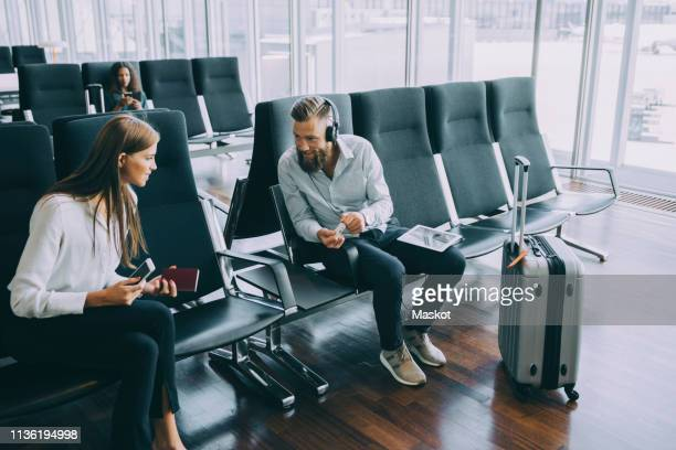 Smiling businessman talking to businesswoman while sitting at waiting room in airport