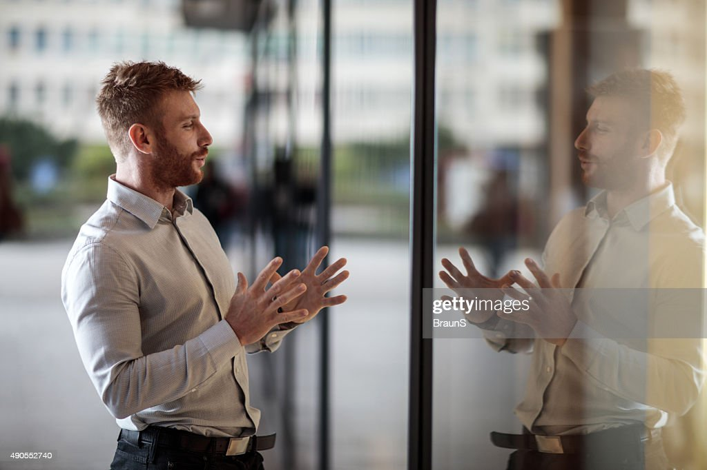 Smiling businessman talking to his reflection in window display. : Stock Photo