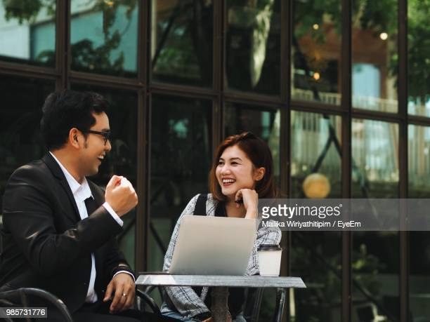 Smiling Businessman Talking With Colleague