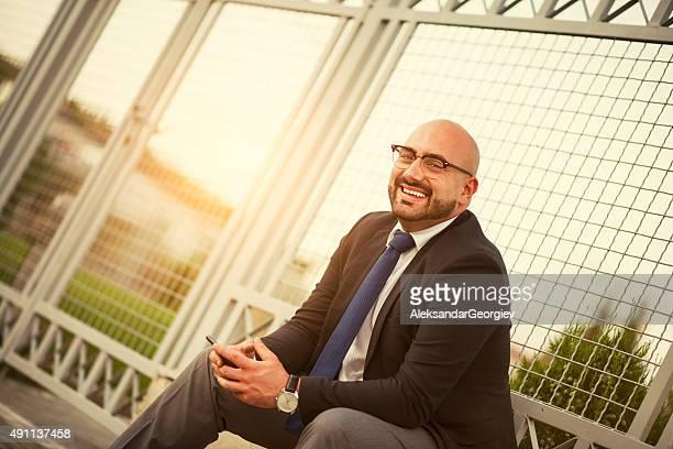 笑顔のスマートフォンを使用して実業家のお仕事からのご休憩