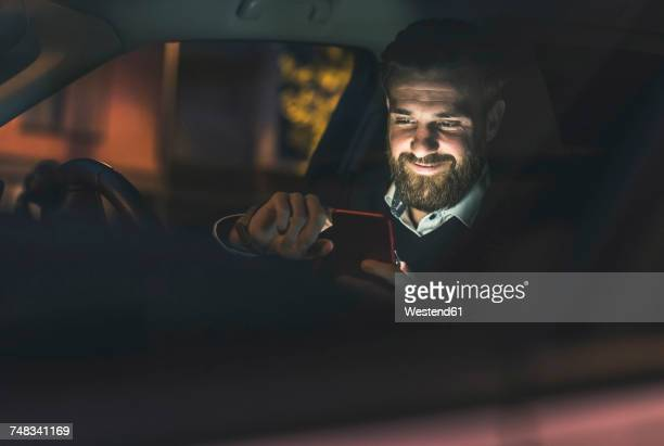 Smiling businessman using cell phone in car at night