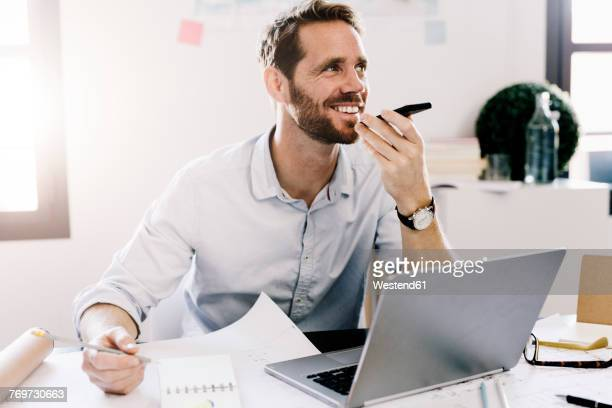 Smiling businessman using cell phone in his office
