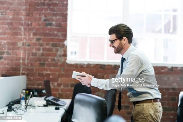 Smiling businessman using digital tablet at office