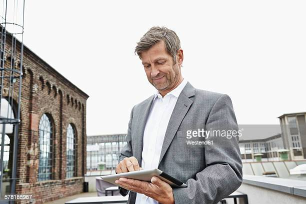 Smiling businessman using digital tablet on roof terrace