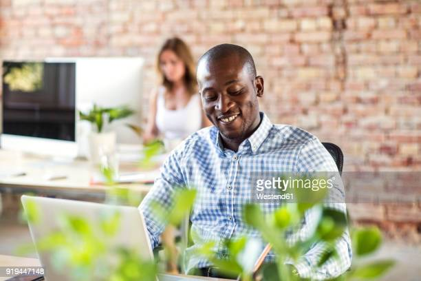 Smiling businessman using laptop at desk in office with colleague in background
