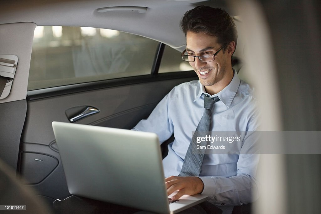 Smiling businessman using laptop in back seat of car at night : Stock Photo