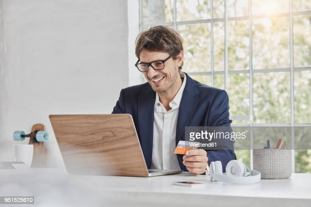 smiling businessman using laptop on desk holding card - charging sports stock pictures, royalty-free photos & images