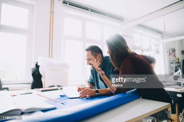 smiling businessman using laptop while discussing with businesswoman at table in creative office - design professional stock pictures, royalty-free photos & images