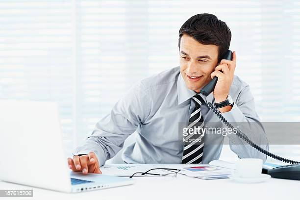 Smiling businessman using laptop while talking on phone in office