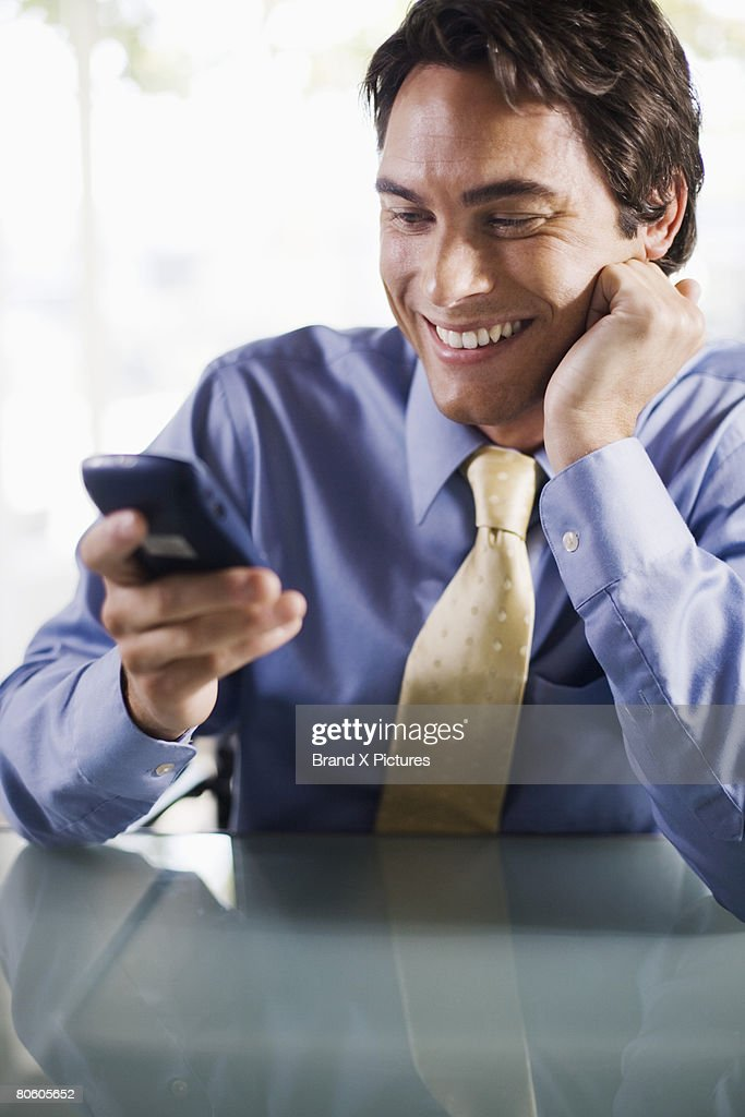 Smiling businessman using PDA : Stock Photo