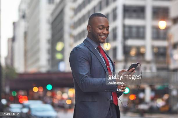 Smiling businessman using smart phone in city