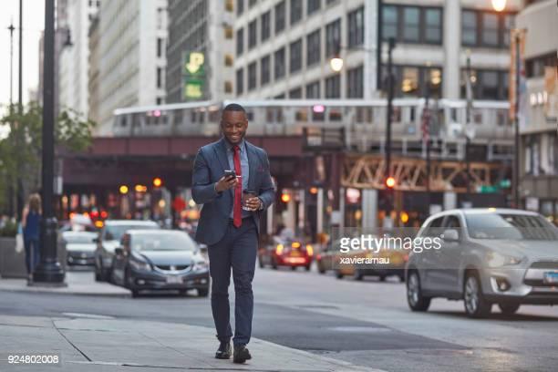 Smiling businessman using smart phone on street