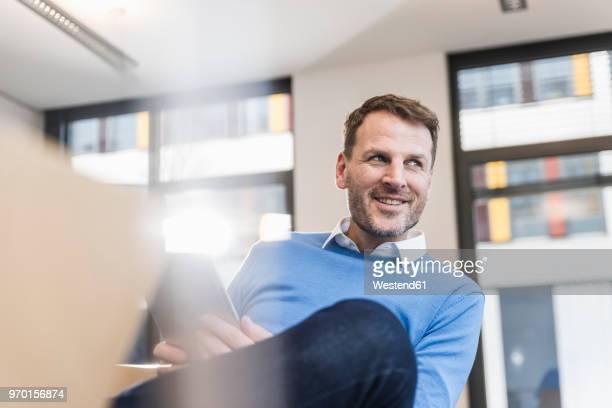 smiling businessman using tablet in office - mise au point sélective photos et images de collection