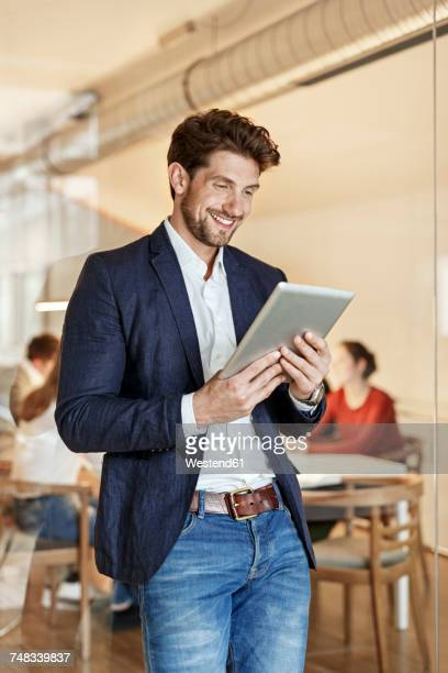 smiling businessman using tablet in office with a meeting in background - incidental people stock pictures, royalty-free photos & images
