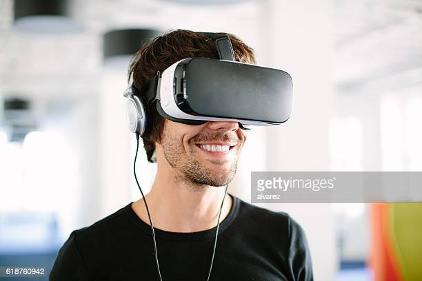 smiling businessman using vr simulator in office - jogo de teste - fotografias e filmes do acervo