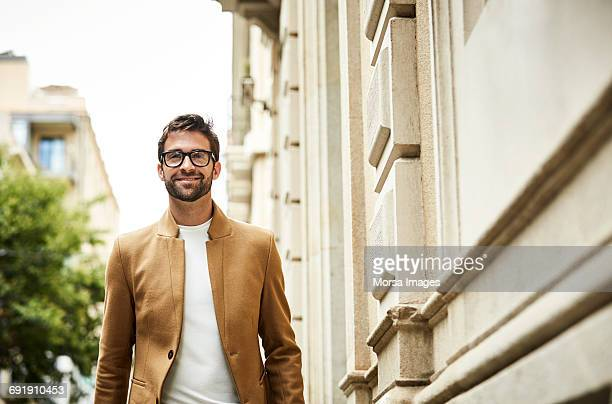 smiling businessman walking by building in city - thick rimmed spectacles stock photos and pictures