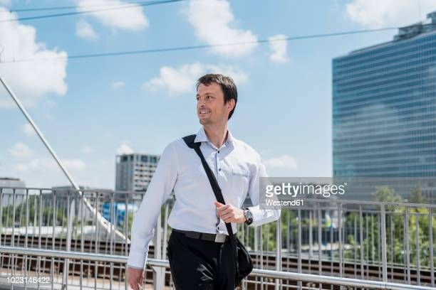 Smiling businessman walking on a bridge