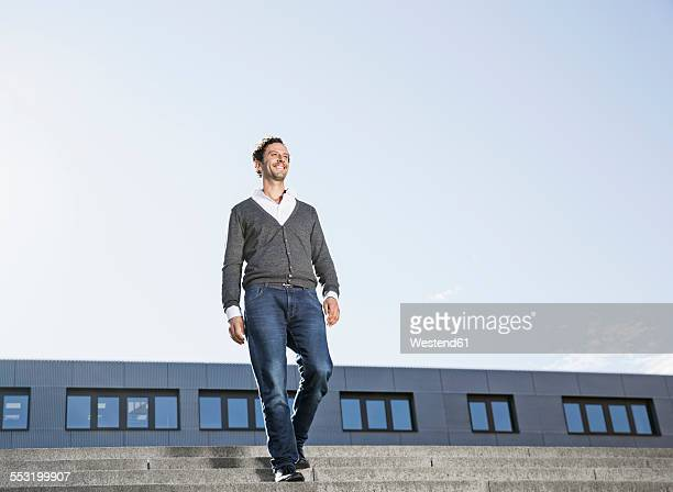 Smiling businessman walking on stairs