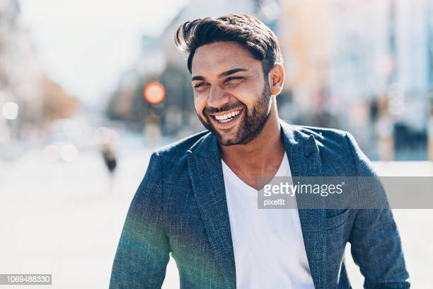 smiling businessman walking outdoors in the city - looking away stock pictures, royalty-free photos & images