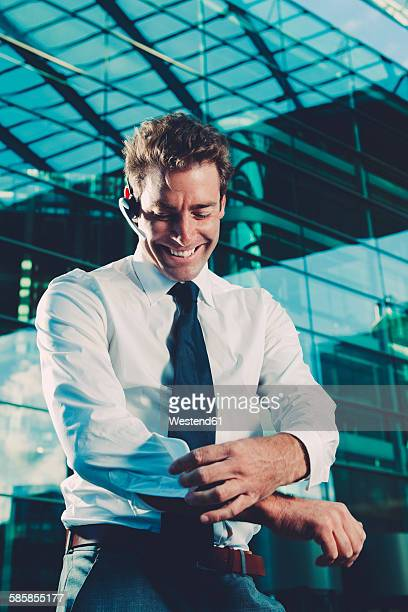 Smiling businessman wearing bluetooth wireless device outside office building