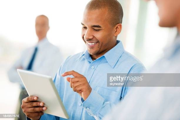 Smiling businessman with a digital tablet in hand