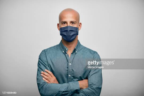 smiling businessman with arms crossed wearing home made face mask. - studio shot stockfoto's en -beelden