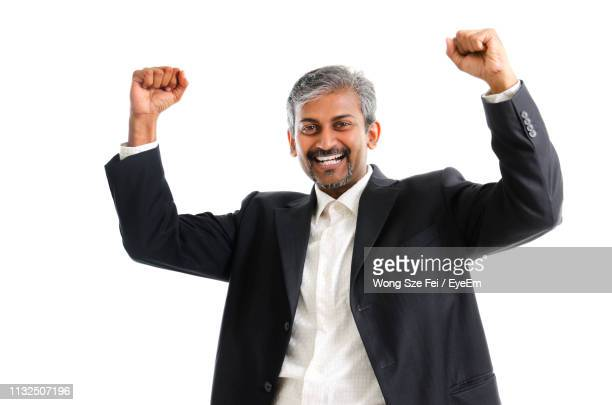smiling businessman with arms raised standing against white background - gesturing stock pictures, royalty-free photos & images