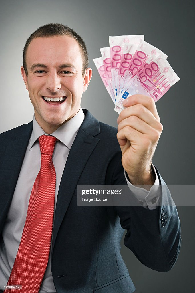 Smiling businessman with bank notes : Stock Photo