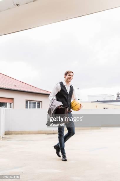 smiling businessman with basketball walking at parking garage - ベスト ストックフォトと画像