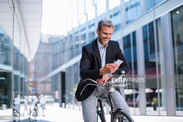 Smiling businessman with bicycle and cell phone in the city