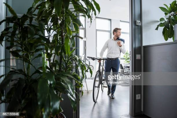 Smiling businessman with bicycle in the office