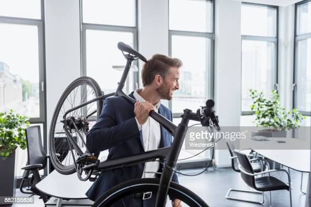 Smiling businessman with bicycle on his shoulder in the office