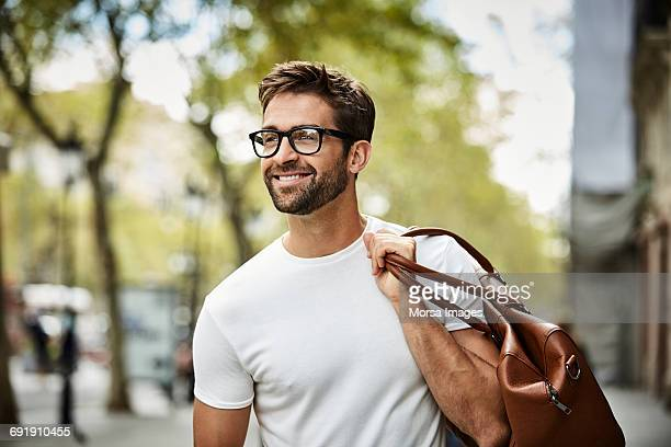 smiling businessman with brown bag walking in city - mooie mensen stockfoto's en -beelden