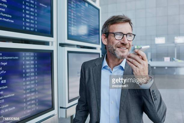 Smiling businessman with cell phone at timetable at the airport