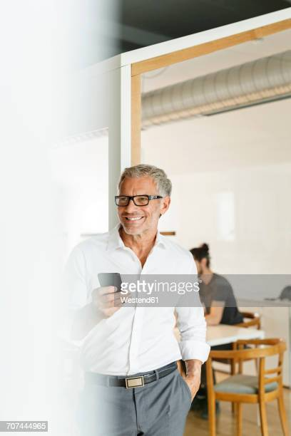 Smiling businessman with cell phone in office