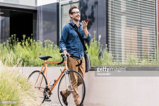 smiling businessman with cell phone pushing bicycle - fahrrad stock-fotos und bilder