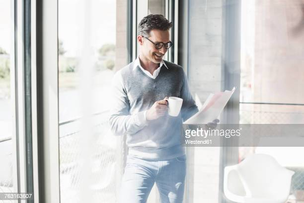 Smiling businessman with coffee mug looking at documents in an office