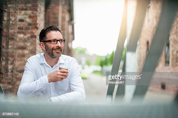 Smiling businessman with coffee to go