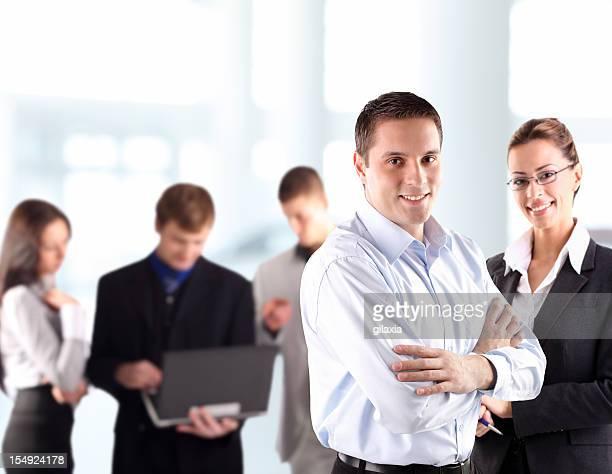 uomo d'affari sorridente con i colleghi in background. - gilaxia foto e immagini stock