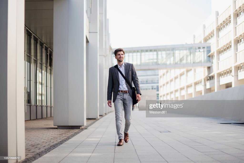 Smiling businessman with crossbody bag in the city on the move : Stock Photo