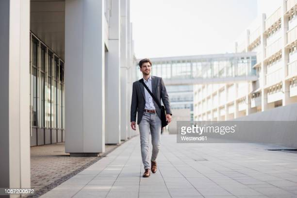 smiling businessman with crossbody bag in the city on the move - alleen één jonge man stockfoto's en -beelden