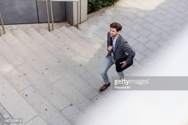 smiling businessman with crossbody bag walking upstairs - staircase stock-fotos und bilder