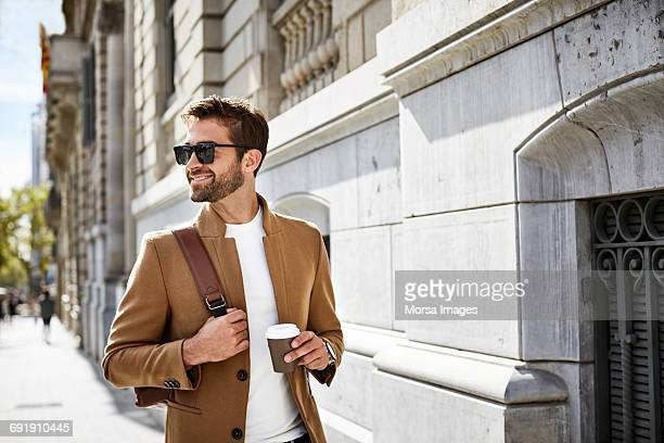 smiling businessman with cup looking away in city - shoulder bag stock pictures, royalty-free photos & images