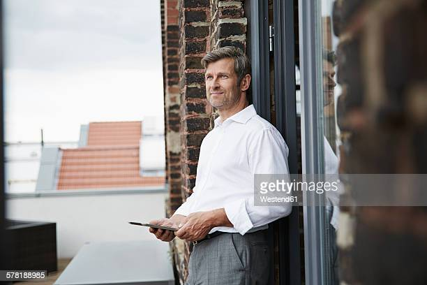 Smiling businessman with digital tablet on roof terrace