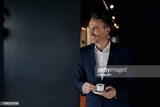 smiling businessman with espresso cup looking sideways - espresso stock pictures, royalty-free photos & images