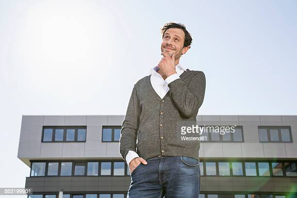 Smiling businessman with hand on chin looking up