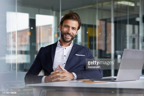 smiling businessman with hands clasped sitting by desk in office - suit stock pictures, royalty-free photos & images