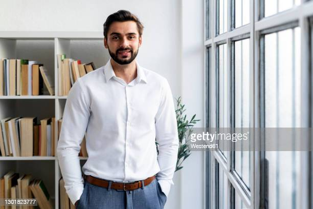 smiling businessman with hands in pockets standing against bookshelf in office - white shirt stock pictures, royalty-free photos & images