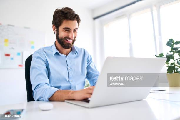 smiling businessman with headphones sitting at a desk using a laptop - gifted movie stock pictures, royalty-free photos & images