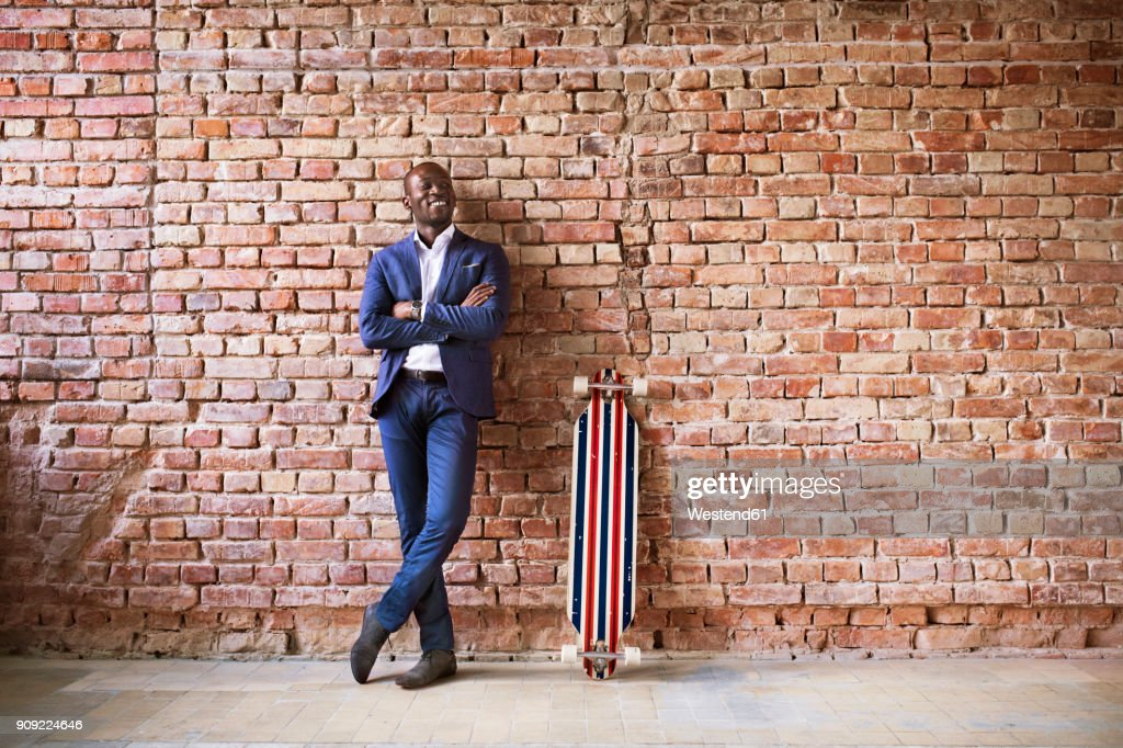 Smiling businessman with longboard at brick wall : Stock Photo